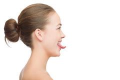 Puts out tongue. Fun girl profile puts out the tongue on white background with copyspace isolated Stock Images