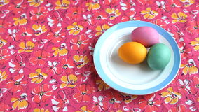 She puts on a pink tablecloth saucer with colorful Easter eggs. stock footage