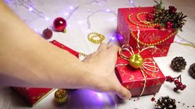 Puts red hand-made gift boxes and Christmas decorations, golden apples and bumps with shimmering lanterns, top view stock video