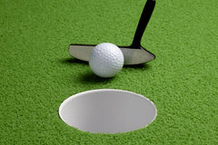 Putt. Close up shot of putter tapping in a golf ball on the green Stock Photography