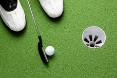 The putt. Golfer about to putt ball into cup on green Stock Images