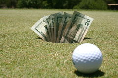 Putt for dough. A golf ball in front of a hole with cash Royalty Free Stock Photos
