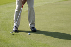 Putt Practice. A golfer wearing beige pants and black leather shoes practicing his putt on a sunny day Stock Photography