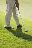 Putt Practice. A golfer wearing beige pants and black leather shoes practicing his putt without a ball on a sunny day Royalty Free Stock Photo