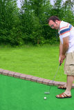 Putt Putt Golf. A man lining up a putt on a miniature golf course Royalty Free Stock Photo