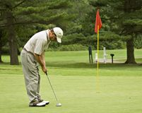 Putt Shot. Man on green putting golf ball toward red flag royalty free stock photos