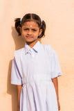 PUTTAPARTHI,安得拉邦,印度- 2017年7月9日:一个逗人喜爱的印地安女孩的画象白色礼服的 特写镜头 垂直 库存照片