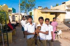 PUTTAPARTHI,安得拉邦-印度- 2016年11月09日:印地安入学年龄男孩穿戴的制服摆在街道,室外 免版税库存图片