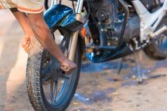 PUTTAPARTHI,安得拉邦-印度- 2016年11月09日:摩托车和一个人,特写镜头的手的轮子 库存图片