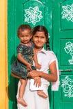PUTTAPARTHI, АНДХРА-ПРАДЕШ, ИНДИЯ - 9-ОЕ ИЮЛЯ 2017: Индийская девушка с малым ребенком вертикально Конец-вверх Стоковая Фотография RF