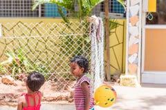 PUTTAPARTHI, АНДХРА-ПРАДЕШ, ИНДИЯ - 9-ОЕ ИЮЛЯ 2017: Индийские девушки играя на улице Скопируйте космос для текста Стоковое Фото