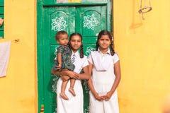 PUTTAPARTHI, АНДХРА-ПРАДЕШ, ИНДИЯ - 9-ОЕ ИЮЛЯ 2017: 2 индийских девушки с ребенком на пороге дома Скопируйте космос для текста Стоковая Фотография
