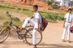 PUTTAPARTHI, АНДХРА-ПРАДЕШ, ИНДИЯ - 9-ОЕ ИЮЛЯ 2017: 2 индийских мальчика на велосипедах Скопируйте космос для текста Стоковая Фотография RF