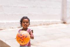 PUTTAPARTHI, ANDHRA PRADESH, ÍNDIA - 9 DE JULHO DE 2017: Menina indiana feliz que joga na rua Copie o espaço para o texto Foto de Stock Royalty Free