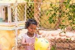PUTTAPARTHI, ANDHRA PRADESH, ÍNDIA - 9 DE JULHO DE 2017: Menina indiana feliz que joga na rua Copie o espaço para o texto Fotografia de Stock