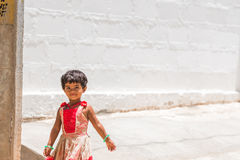 PUTTAPARTHI, ANDHRA PRADESH, INDIA - JULY 9, 2017: Happy indian girl playing on the street. Copy space for text. Stock Photos