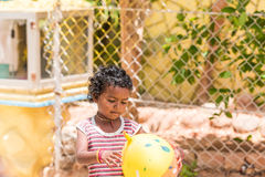 PUTTAPARTHI, ANDHRA PRADESH, INDIA - JULY 9, 2017: Happy indian girl playing on the street. Copy space for text. Stock Photography