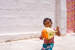 PUTTAPARTHI, ANDHRA PRADESH, INDIA - JULY 9, 2017: Happy indian girl playing on the street. Copy space for text. Royalty Free Stock Photo