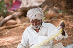 PUTTAPARTHI, ANDHRA PRADESH, INDIA - JULY 9, 2017: Rustic old man in a traditional white dress with a fishing net. Close-up. stock image