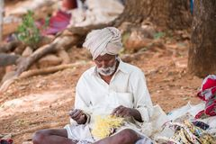 PUTTAPARTHI, ANDHRA PRADESH, INDIA - JULY 9, 2017: Rustic old man in a traditional white dress with a fishing net. Close-up. PUTTAPARTHI, ANDHRA PRADESH, INDIA Stock Photo