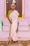 PUTTAPARTHI, ANDHRA PRADESH, INDIA - 9 LUGLIO 2017: Una donna indiana anziana al gradino della porta di una casa Copi lo spazio p Immagine Stock