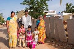 PUTTAPARTHI ANDHRA PRADESH, INDIEN - JULI 9, 2017: Indisk familj i en bygata Kopiera utrymme för text Fotografering för Bildbyråer