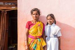 PUTTAPARTHI, ANDHRA PRADESH, LA INDIA - 9 DE JULIO DE 2017: Mujer india en sari y muchacha en uniforme escolar Copie el espacio p foto de archivo