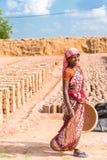 PUTTAPARTHI, ANDRA PRADESH, INDIA - JULI 9, 2017: Indische vrouw op een achtergrond van het drogen van bakstenen Exemplaarruimte  Royalty-vrije Stock Foto's