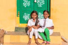 PUTTAPARTHI, ANDRA PRADESH, INDIA - JULI 9, 2017: Twee leuke Indische meisjeszitting op de drempel Exemplaarruimte voor tekst Stock Foto