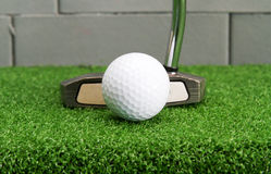 Putter address at golf ball on artificial grass. Stock Image
