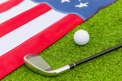 Putter and ball lie on  grass near to a flag of America Royalty Free Stock Images