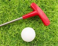 Putter et boule de golf rouges sur un fond d'herbe verte Photo stock
