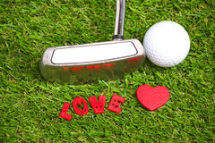 Putter and golf ball on green background. Putter and golf ball are on green background Stock Photo