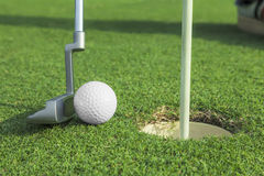 Putter puts a golf ball to hole Stock Image