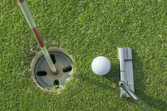 Putter puts a golf ball to hole. On green of golf course Royalty Free Stock Photo