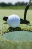 Putter, sfera e verde di golf Immagine Stock
