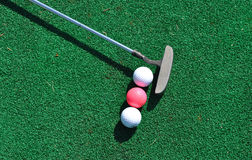 Putter and three golf balls Royalty Free Stock Photo