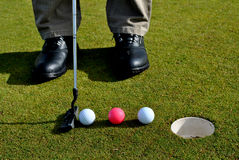 Putter and three golf balls. Man practicing golf with a putter and three golf balls Stock Photos