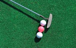 Putter und drei Golfbälle Lizenzfreies Stockfoto