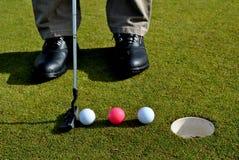 Putter und drei Golfbälle Stockfotos