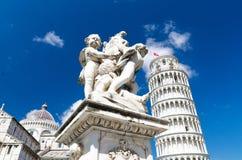 Putti springbrunn, Pisa domkyrkaDuomo Cattedrale och benägenhettorn Torre på den Piazza del Miracoli fyrkanten royaltyfri foto