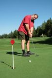 Putting. Ederly man putting a ball in a hole Stock Photo