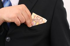 Putting 50 Euro in the own pocket. Businessman in black suit putting 50 Euro in the own pocket Royalty Free Stock Photography