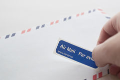 Putting air mail tag on envelope. One white background Royalty Free Stock Photo