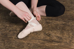 Putting ballet shoes. Young ballerina or dancer girl putting on her ballet shoes on the wooden floor. Female dancer ties on her pink ballet slippers with ribbons stock image