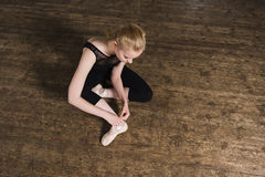 Putting ballet shoes. Young ballerina or dancer girl putting on her ballet shoes on the wooden floor. Female dancer ties on her pink ballet slippers with ribbons stock photos