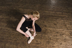 Putting ballet shoes. Young ballerina or dancer girl putting on her ballet shoes on the wooden floor. Top view royalty free stock photos