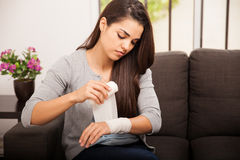 Putting a bandage on her arm Royalty Free Stock Photo