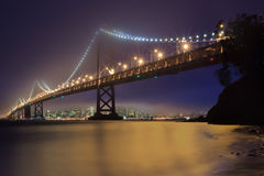 Putting the Bay Bridge to Sleep. The Historic Bay Bridge in San Francisco California stands large agains the fog with the illuminated city in the backgound Royalty Free Stock Photos