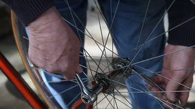 Putting bike wheel back on stock footage